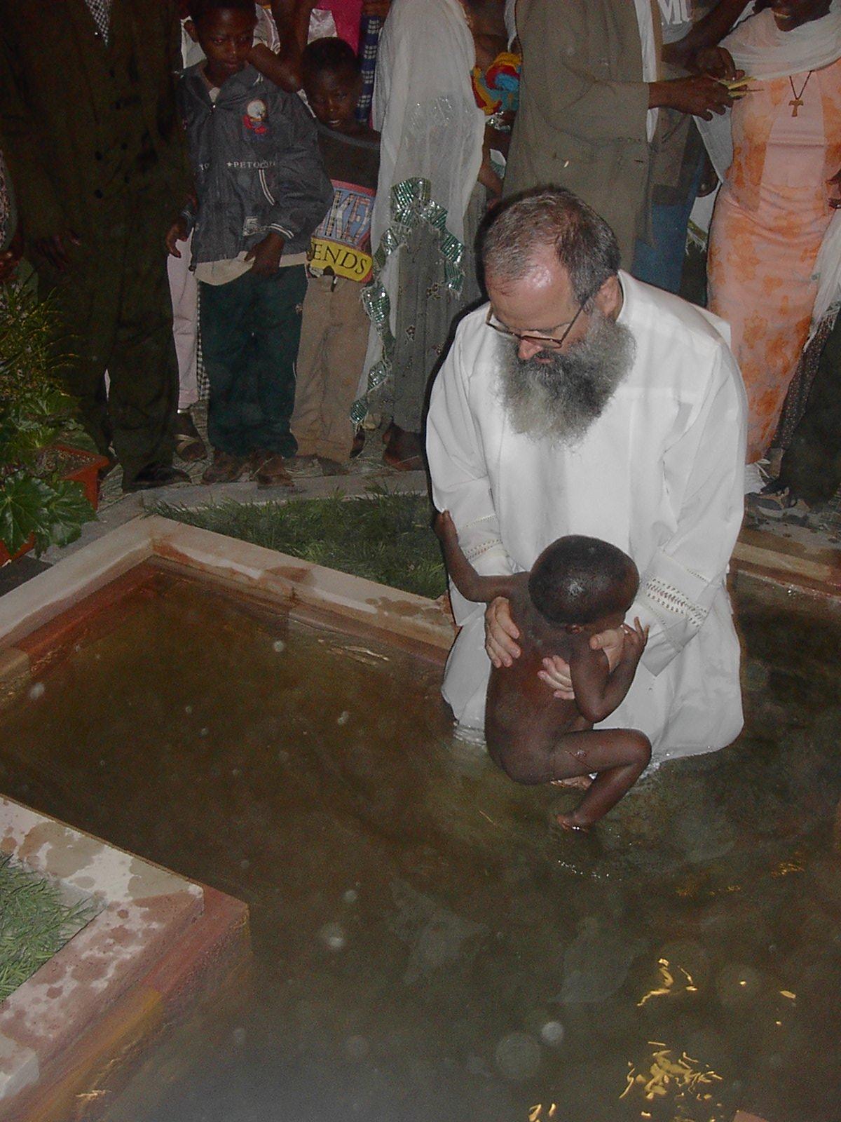 Padre Angelo battezza un bambino etiope